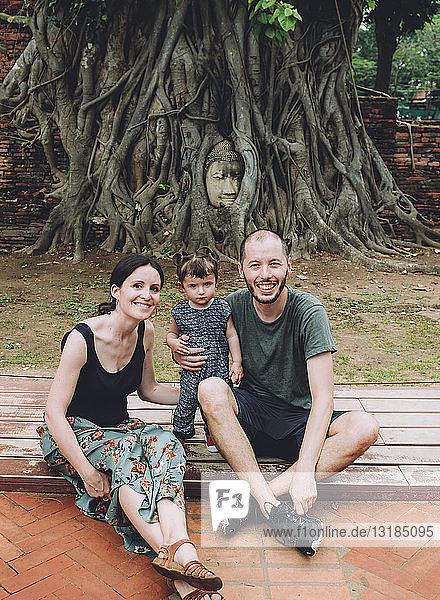 Thailand  Ayutthaya  portrait of smiling family visiting the Buddha head in between tree roots at Wat Mahathat