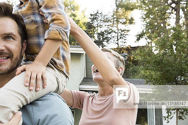 Glückliche Eltern mit Sohn vor ihrem Haus