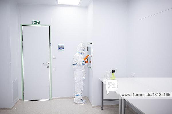 Labortechniker trägt Reinraumoverall an der Materialschleuse