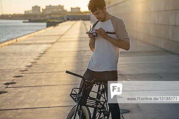 Junger Mann mit Pendler-Fixie-Fahrrad und Kamera auf der Uferpromenade am Flussufer