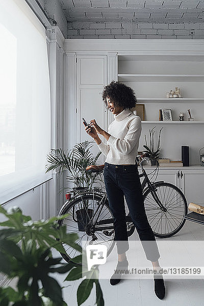 Mittlere erwachsene Freiberuflerin  die in ihrem Heimbüro steht und ein Smartphone benutzt