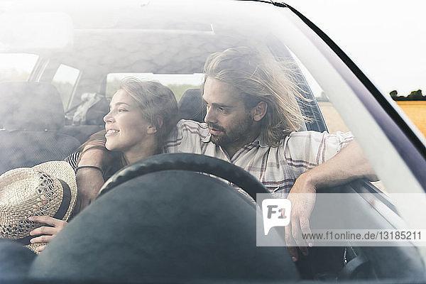 Zärtliches junges Paar in einem Auto