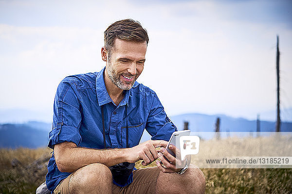 Smiling man resting and checking his cell phone during hiking trip