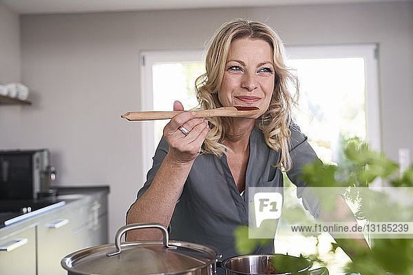 Smiling woman cooking in kitchen tasting tomato sauce