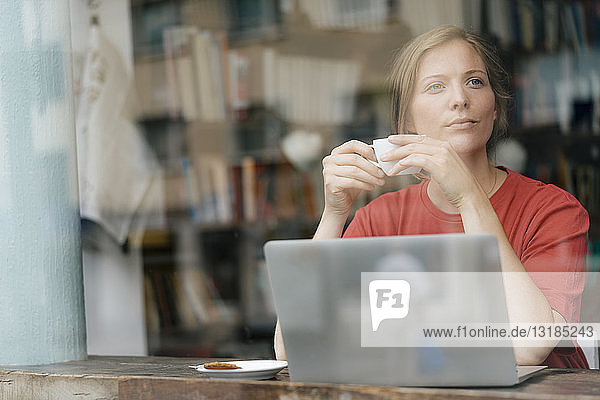 Young woman with cup of coffee and laptop in a cafe