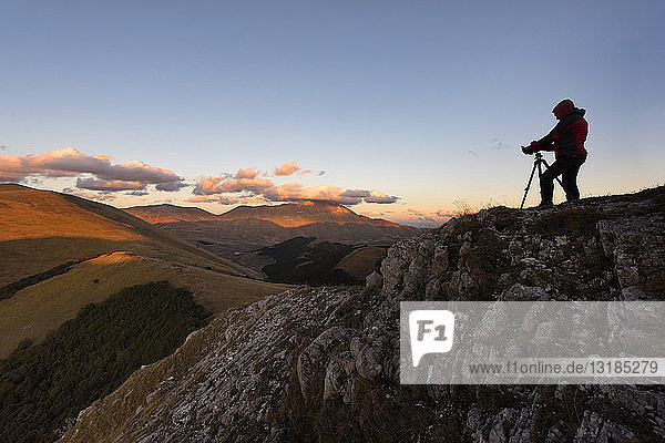 Italy  Umbria  Parco Nazionale dei Monti Sibillini  Photographer in front of Mount Vettore at sunset