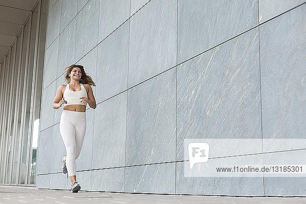 Joggende junge Frau in Weiß gekleidet