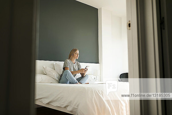 Young woman sitting on bed using cell phone