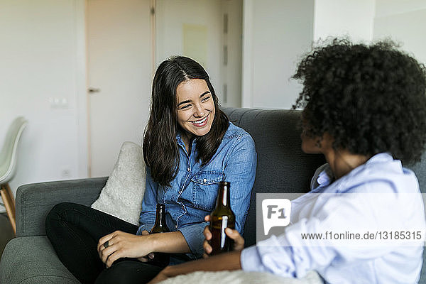 Girlfriends sitting on couch socializing and drinking beer