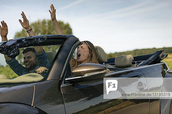 Glückliches Paar fährt mit einem Cabriolet auf einer Landstraße