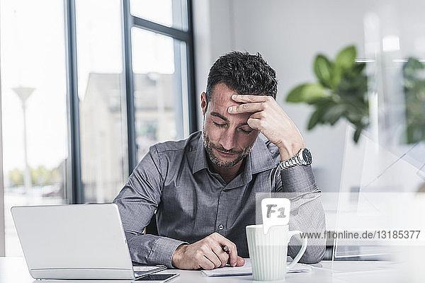Müde Geschäftsmann sitzt im Büro