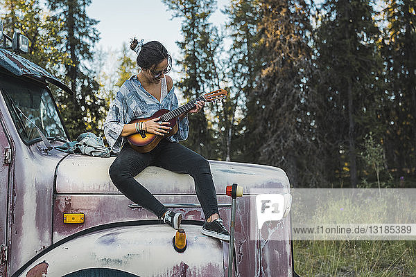 Young woman sitting on a broken truck  playing the ukulele