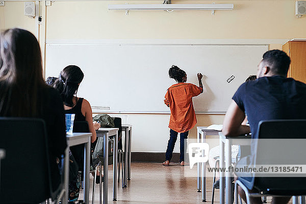 Rear view of female teacher writing on whiteboard in classroom