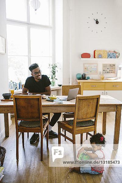 Kleines Mädchen spielt mit Spielzeugauto  während der Vater im Haus am Esstisch sitzt