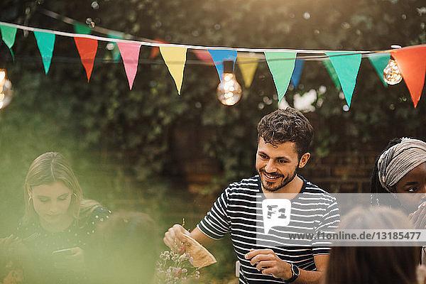 Lächelnder junger Mann genießt Dinnerparty mit Freunden im Hinterhof