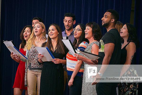 Freundinnen und Freunde halten Notenblätter in der Hand und proben auf der Bühne