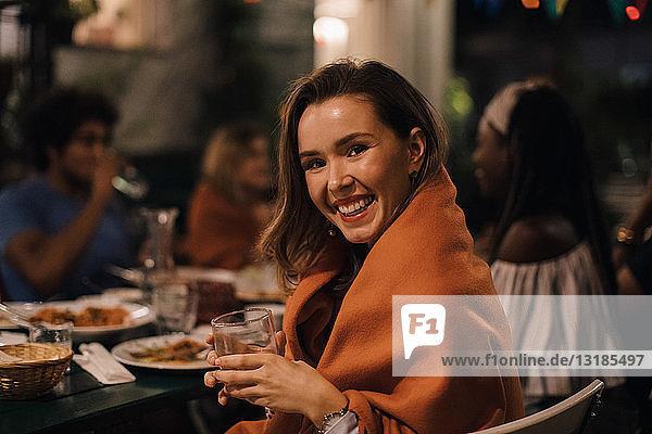 Porträt einer lächelnden jungen Frau  die während einer Dinnerparty im Hinterhof ein Getränk in der Hand hält  während sie am Tisch sitzt