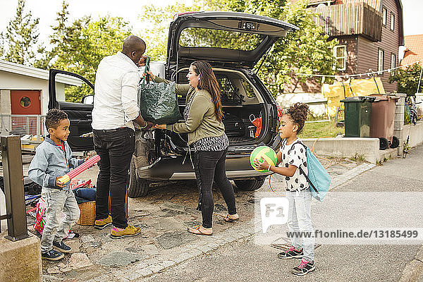Siblings playing while parents loading luggage in car trunk on driveway