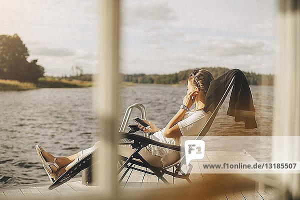 Frau in voller Länge trägt Kopfhörer  während sie auf der Terrasse durch ein Fenster gesehen ein Mobiltelefon benutzt