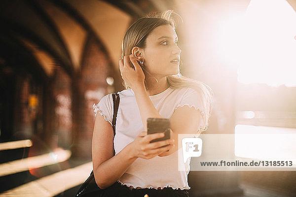 Junge Frau schaut weg  während sie bei strahlendem Sonnenschein auf einem Fußweg in der Stadt ihr Handy in der Hand hält