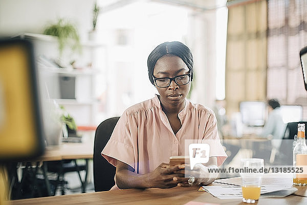 Creative young businesswoman using mobile phone at desk in office