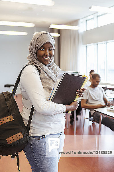 Portrait of smiling woman in hijab standing with books at university classroom