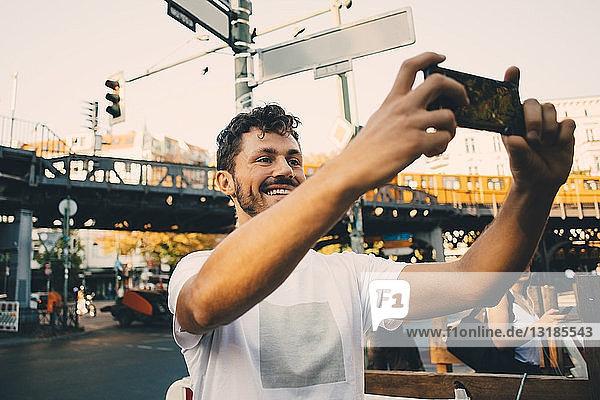 Lächelnder junger Mann fotografiert durch ein Smartphone  während er in der Stadt auf der Straße steht