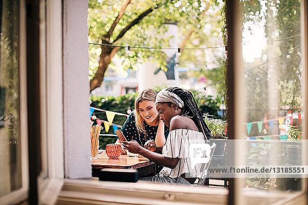 Multi-ethnische Freundinnen schauen durch Fenster auf Handy