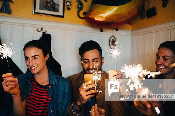 Junge multiethnische männliche und weibliche Freunde mit brennenden Wunderkerzen im Restaurant während der Dinnerparty