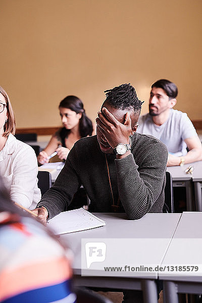 Gelangweilter junger Mann schreibt  während er am Schreibtisch in der Sprachschule sitzt