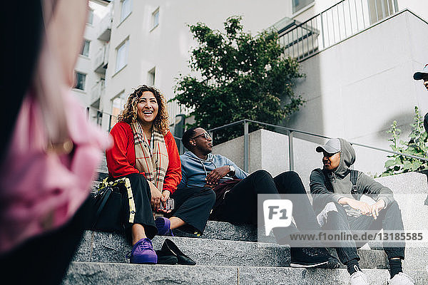 Smiling male and female friends sitting on steps in city