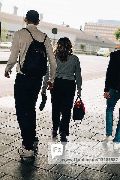 Rear view of friends walking on street in city