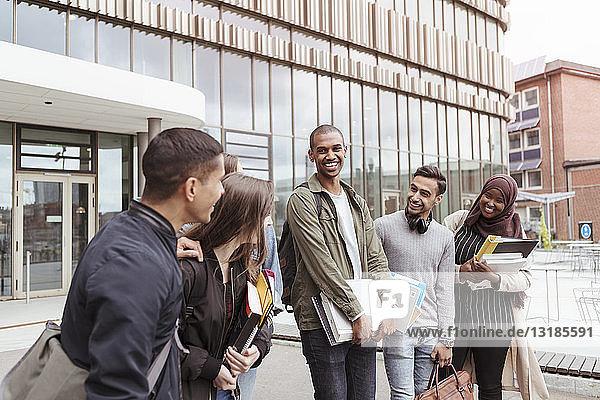Lächelnde Freunde unterhalten sich im Stehen auf dem Universitätscampus