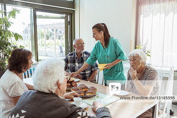 Altenpflegerin  die Menschen am Tisch in einem Pflegeheim Mahlzeiten serviert