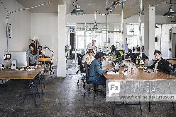 Multi-ethnische Geschäftsleute  die an Schreibtischen im Büro arbeiten