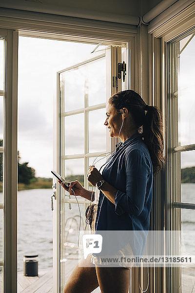 Nachdenklich lächelnde Frau  die in der Ferienvilla stehend über Kopfhörer am Smartphone spricht