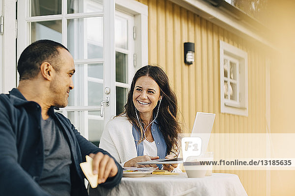 Smiling woman showing laptop to man while sitting at table in patio