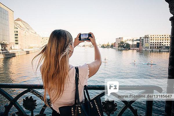 Rückansicht einer jungen Frau  die mit einem Mobiltelefon in der Stadt einen Fluss fotografiert