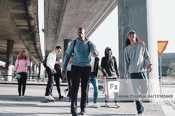 Freunde in voller Länge unter der Überführung auf der Stadtstraße