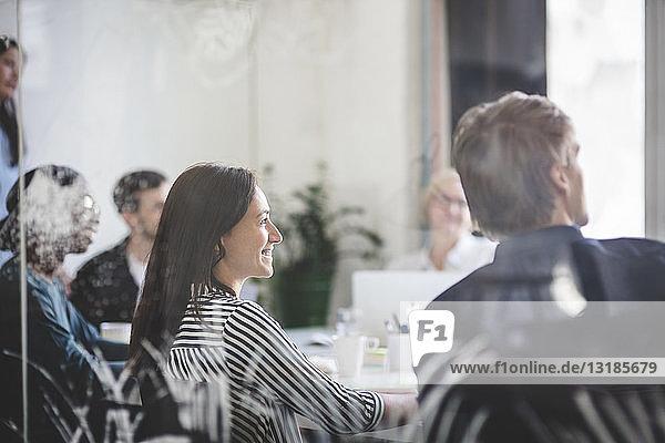 Lächelnde Geschäftsleute hören zu  während sie während des Brainstormings im Sitzungssaal sitzen