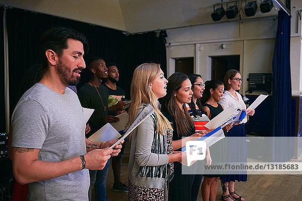 Freunde und Freundinnen mit Notenblättern  die bei der Chorprobe singen