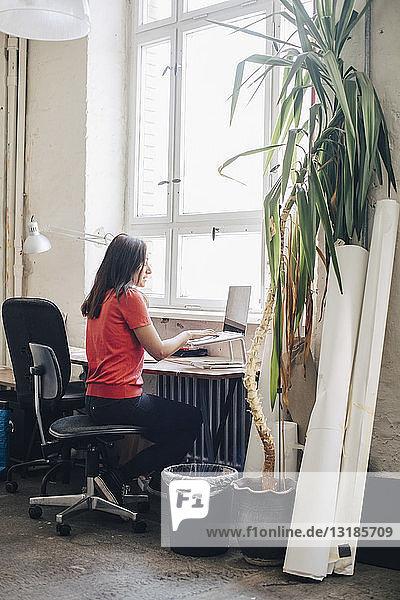 Seitenansicht einer Geschäftsfrau mit Laptop am Schreibtisch im Kreativbüro