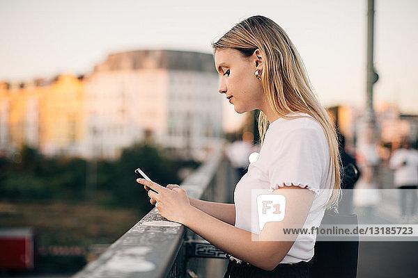 Seitenansicht einer jungen Frau  die ein Smartphone benutzt  während sie auf einer Brücke in der Stadt steht