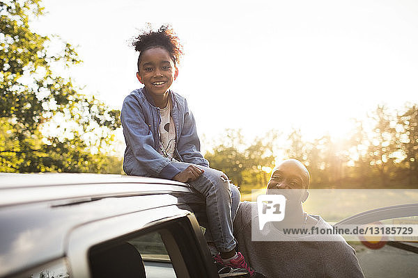 Portrait of smiling girl sitting on car roof by father against clear sky during sunset at park