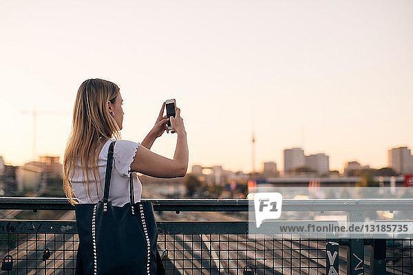 Junge Frau fotografiert durch ein Mobiltelefon  während sie bei Sonnenuntergang auf einer Brücke vor klarem Himmel steht