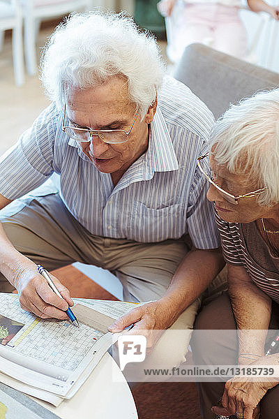 High angle view of senior couple doing crossword puzzle in newspaper at nursing home