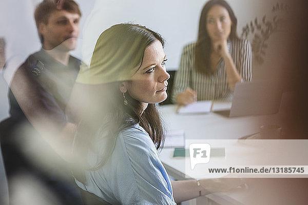 Geschäftsfrau mit Kollegen  die während einer Besprechung im Büro am Konferenztisch sitzen und zuhören