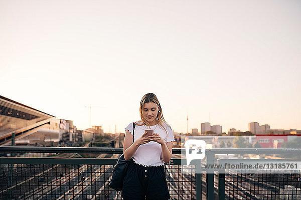Junge Frau benutzt Mobiltelefon  während sie auf der Brücke gegen den klaren Himmel in der Stadt steht