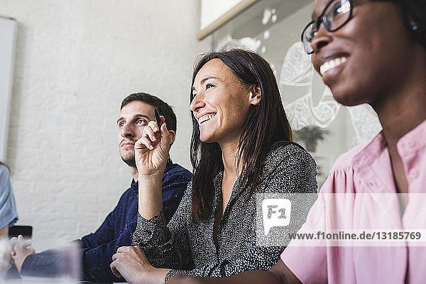 Lächelnde kreative Geschäftsleute hören zu  während sie während der Sitzung im Sitzungssaal sitzen