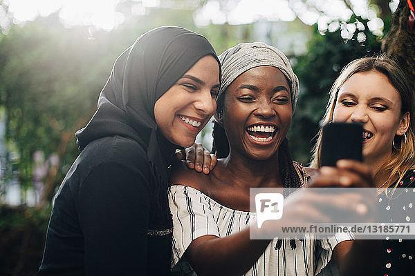 Lächelnde multiethnische Freundinnen  die sich im Hinterhof per Mobiltelefon selbstständig machen